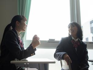 教室で会話する2人の女子高校生の写真素材 [FYI01220701]