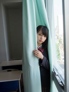 カーテンに包まる女子高校生の写真素材 [FYI01220713]