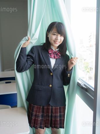 カーテンに包まる女子高校生の写真素材 [FYI01220714]