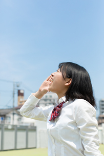 空に向かって大声で叫ぶ女子高校生の写真素材 [FYI01220729]