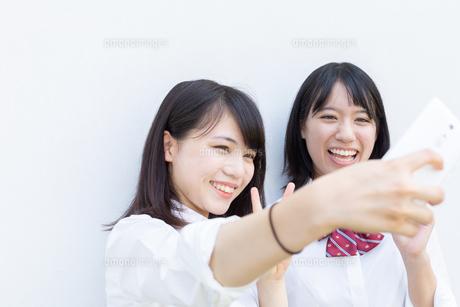 スマートフォンで自撮りする2人の女子高校生の写真素材 [FYI01220732]