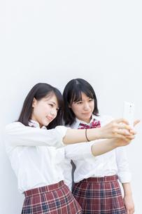 スマートフォンで自撮りする2人の女子高校生の写真素材 [FYI01220733]
