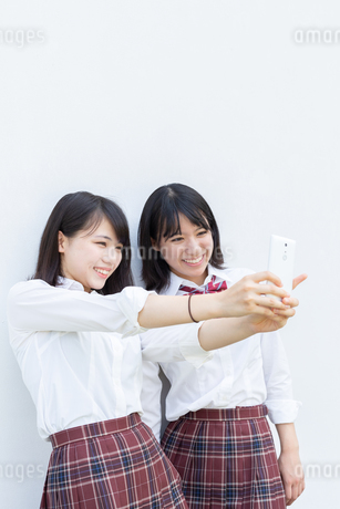 スマートフォンで自撮りする2人の女子高校生の写真素材 [FYI01220734]