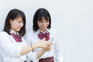 スマートフォンの画面を見る2人の女子高校生の写真素材 [FYI01220735]