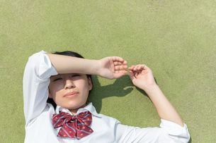 寝転ぶ笑顔の女子高校生の写真素材 [FYI01220738]