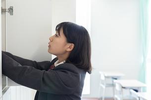 教室のロッカーに手を入れる女子高校生の写真素材 [FYI01220766]