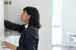 教室のロッカーに手を入れる女子高校生の写真素材 [FYI01220767]