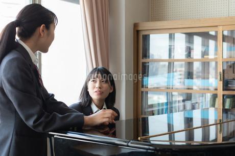 ピアノの前で会話する女子高校生の写真素材 [FYI01220777]