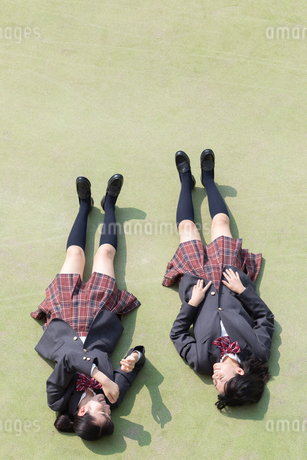 校庭で仰向けに寝転ぶ2人の女子高校生の写真素材 [FYI01220785]