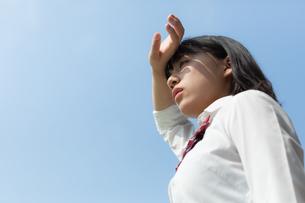 顔に手をかざす女子高校生の写真素材 [FYI01220790]