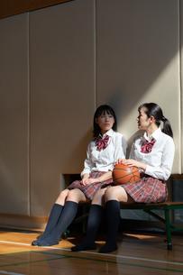 ベンチに座って会話する2人の女子高校生の写真素材 [FYI01220802]