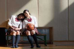 ベンチに座って寄り添う2人の女子高校生の写真素材 [FYI01220804]