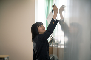 ホワイトボードの前の女子高校生の写真素材 [FYI01220842]