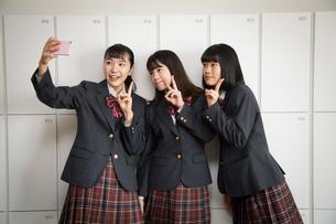 スマートフォンで自撮りする3人の女子高校生の写真素材 [FYI01220844]