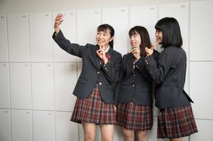 スマートフォンで自撮りする3人の女子高校生の写真素材 [FYI01220845]
