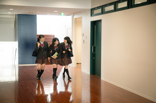 廊下を歩く3人の女子高校生の写真素材 [FYI01220852]