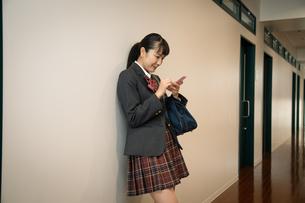 スマートフォンを操作する女子高校生の写真素材 [FYI01220858]