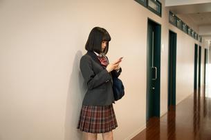 スマートフォンを操作する女子高校生の写真素材 [FYI01220860]