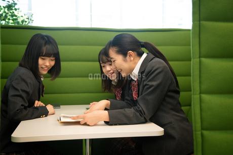 テーブルで本を見る3人の女子高校生の写真素材 [FYI01220868]