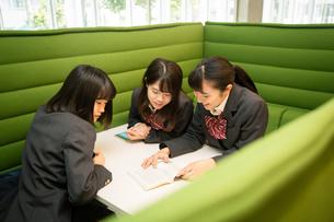 テーブルで本を見る3人の女子高校生の写真素材 [FYI01220870]