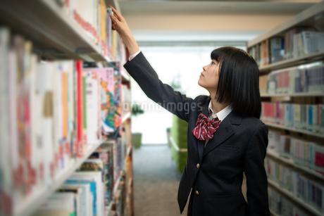図書室で本を選ぶ女子高校生の写真素材 [FYI01220872]