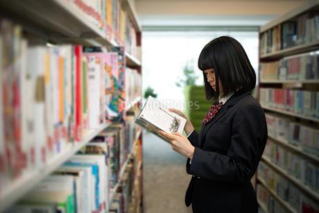 図書室で本を読む女子高校生の写真素材 [FYI01220873]