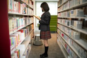 図書室で本を読む女子高校生の写真素材 [FYI01220874]