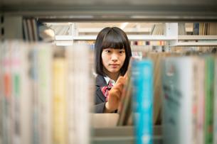 図書室で本を選ぶ女子高校生の写真素材 [FYI01220876]