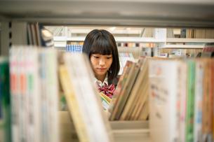 図書室で本を読む女子高校生の写真素材 [FYI01220877]