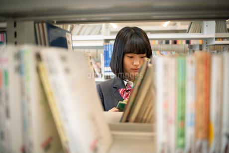 図書室で本を読む女子高校生の写真素材 [FYI01220878]