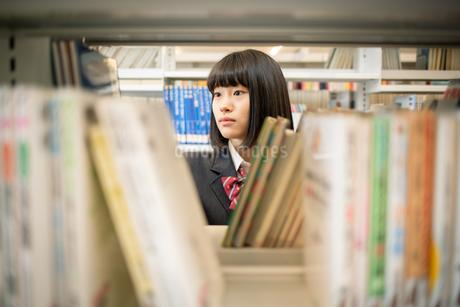 図書室で本を選ぶ女子高校生の写真素材 [FYI01220879]