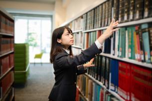 図書室で本を選ぶ女子高校生の写真素材 [FYI01220880]