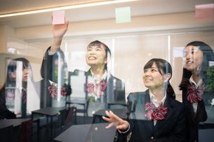 ガラスに付箋を貼る女子高校生の写真素材 [FYI01220883]
