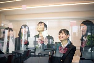 ガラスに付箋を貼る女子高校生の写真素材 [FYI01220884]