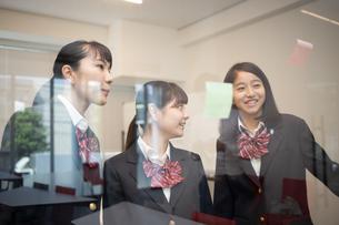 ガラスに付箋を貼る女子高校生の写真素材 [FYI01220885]