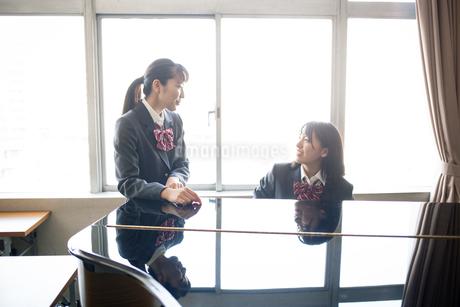 音楽室のピアノの前にいる女子高校生の写真素材 [FYI01220887]