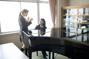 音楽室のピアノの前にいる女子高校生の写真素材 [FYI01220888]