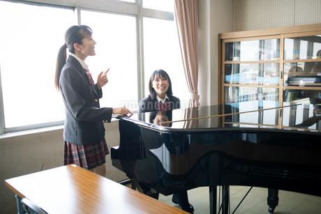 音楽室のピアノの前にいる女子高校生の写真素材 [FYI01220889]