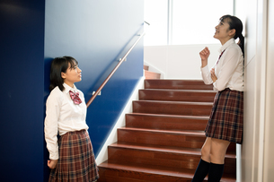 階段で会話する2人の女子高校生の写真素材 [FYI01220958]