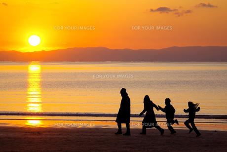 夕日の沈む海岸を楽しそうに歩く4人家族のシルエットの写真素材 [FYI01221121]