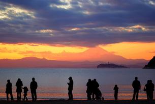 夕日に染まる富士山を海岸から眺める人々のシルエットの写真素材 [FYI01221122]