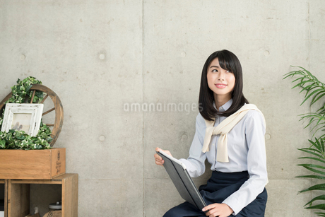iPadを手に持って椅子に座るOL女性の写真素材 [FYI01221393]