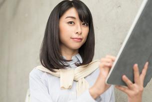 iPadを手に持って指で操作する20代OL女性カメラ目線の写真素材 [FYI01221396]