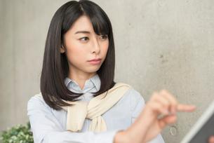 iPadを指で操作する20代OL女性の写真素材 [FYI01221397]