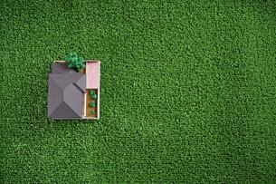 緑の人工芝に置いたミニチュアの家の写真素材 [FYI01222475]