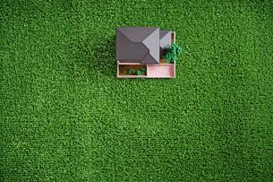緑の人工芝に置いたミニチュアの家の写真素材 [FYI01222476]