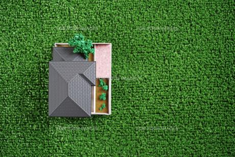 緑の人工芝に置いたミニチュアの家の写真素材 [FYI01222477]