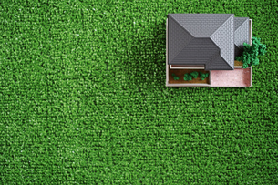 緑の人工芝に置いたミニチュアの家の写真素材 [FYI01222479]