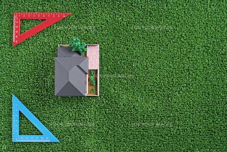 緑の人工芝に置いたミニチュアの家と三角定規の写真素材 [FYI01222480]
