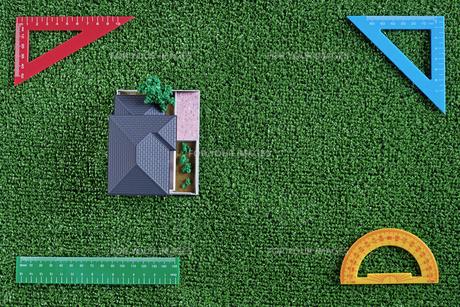 緑の人工芝に置いたミニチュアの家と定規などの文房具の写真素材 [FYI01222482]